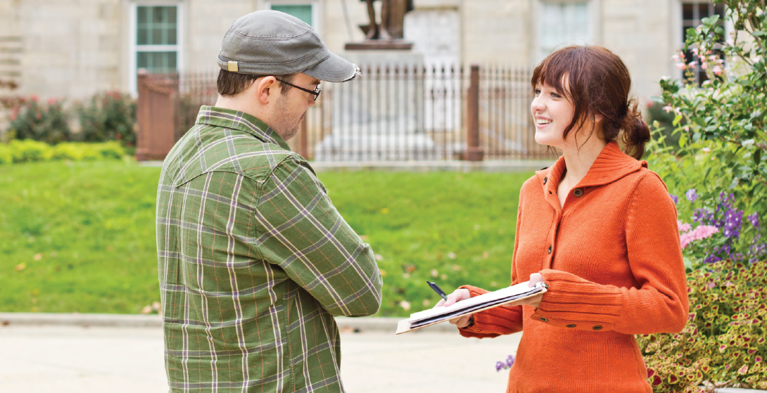 A young woman holding a clipboard interviews a man on the street.