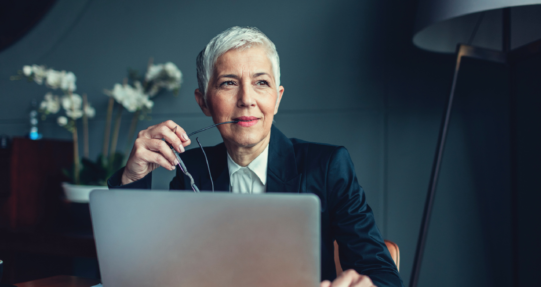 A professional looking middle-aged woman looks thoughtful as she works on a computer.