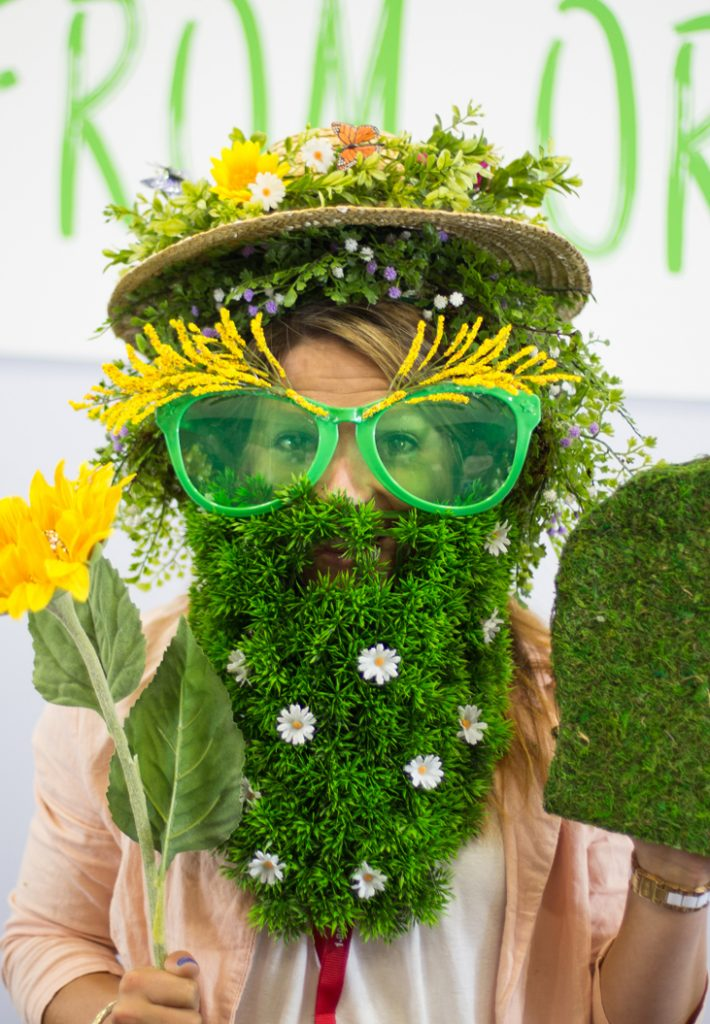 Woman with various plants on her face and giant sunglasses.