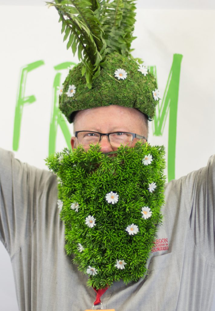 Man with a beard and hat made out of plants.